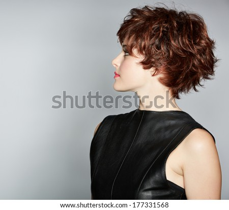 portrait of a young woman in leather top with red hair wearing short pixie crop hairstyle on studio background