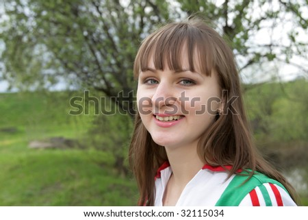 Portrait of a young woman in park - stock photo