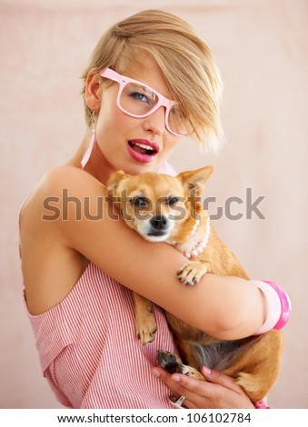 Portrait of a young woman in pink holding a dog - stock photo