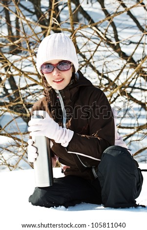 Portrait of a young woman in snowy winter forest, wearing sporty winter clothes, sunglasses, holding a thermos bottle, smiling into camera - stock photo