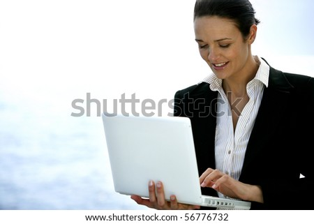 Portrait of a young woman in suit with a laptop computer - stock photo