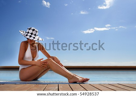 Portrait of a young woman in swimsuit sitting at a poolside - stock photo