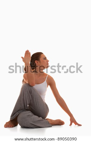 Portrait of a young woman in the Ardha Matsyendrasana position against a white background - stock photo