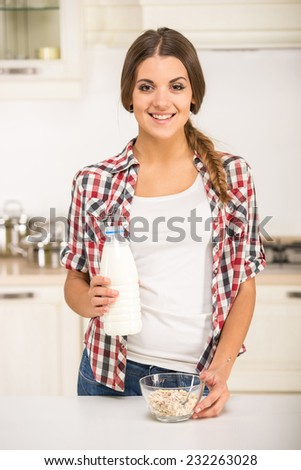 Portrait of a young woman in the kitchen is preparing breakfast.