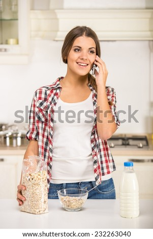 Portrait of a young woman in the kitchen is preparing breakfast and speaking by phone. - stock photo