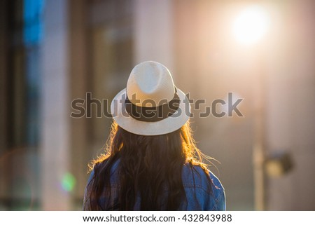 Portrait of a young woman in the light of the street lamps. Girl with hat in profile against the background of the city at night. - stock photo