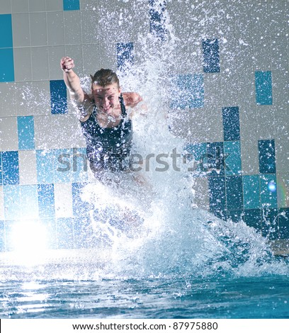 Portrait of a young woman jumping in swimming pool