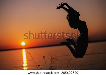 portrait of a Young woman jumping on a beach and doing yoga exercises outdoor - stock photo
