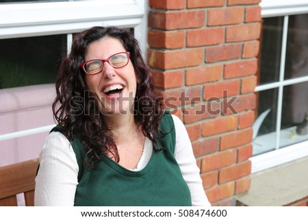 Portrait of a young woman laughing hard wearing glasses and a green dress sitting in front of her house
