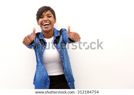 Portrait of a young woman laughing with thumbs up sign - stock photo