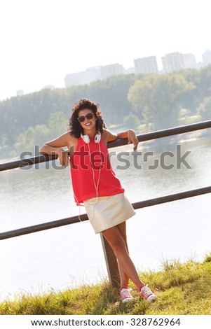 Portrait of a young woman leaning on a fence with a mobile phone in her hand and headphones, along the river.