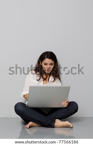 Portrait of a young woman leaning on a wall and using laptop - stock photo