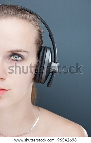 portrait of a young woman listening to music, isolated on gray - stock photo