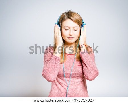 Portrait of a young woman listening to music on headphones, isolated on a gray background