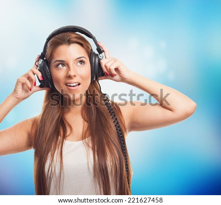 portrait of a young woman listening to music with headphones - stock photo