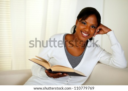 Portrait of a young woman looking at you while holding a book at home indoor