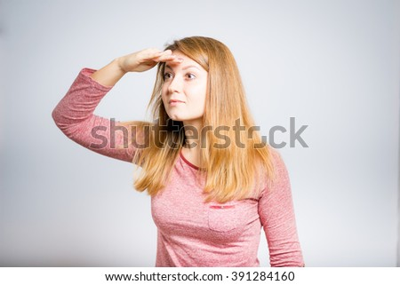 Portrait of a young woman looking into the distance, isolated on a gray background - stock photo