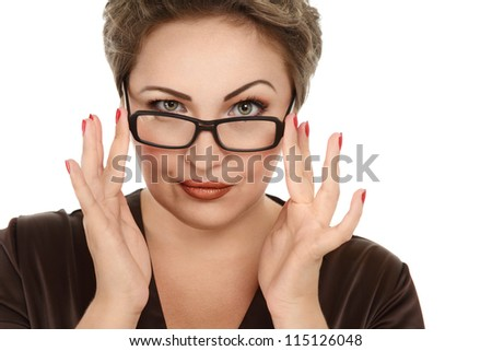 Portrait of a young woman looking over glasses against white background - stock photo