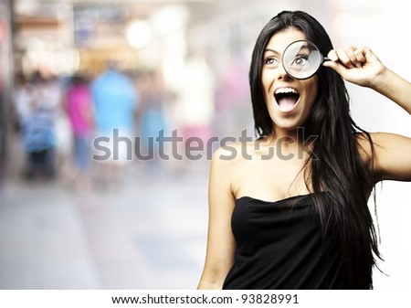 portrait of a young woman looking through a magnifying glass at a crowded place - stock photo