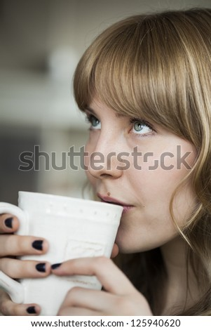 Portrait of a young woman looking up while holding a cup of coffee. - stock photo
