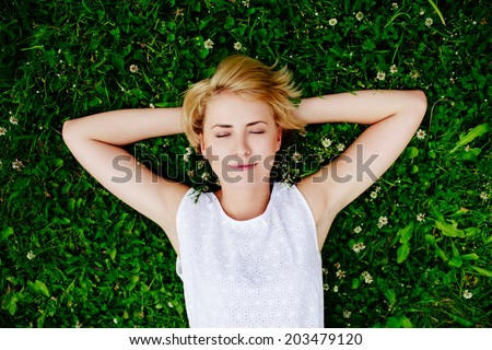Portrait of a young woman lying on the grass - stock photo