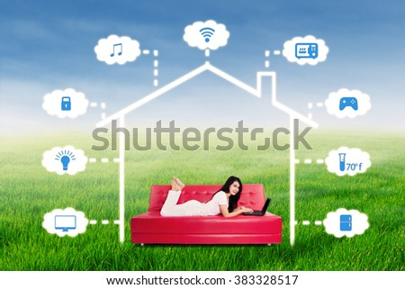 Portrait of a young woman lying on the sofa while using laptop computer to control online home automation system