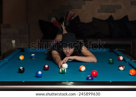 Portrait Of A Young Woman Lying On The Table And Playing Billiards