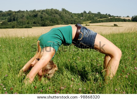 portrait of a young woman making a bridge exercise outdoors in summer - stock photo