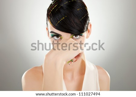 Portrait of a young woman model with nice makeup holding her nose while watching you, against gray background - stock photo