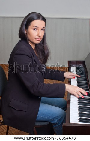 Portrait of a young woman near the piano - stock photo