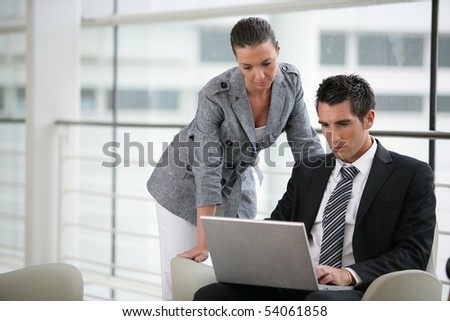 Portrait of a young woman next to a young man with a laptop computer