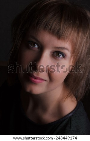 Portrait of a young woman on a black background - stock photo