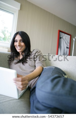 Portrait of a young woman on a sofa with a laptop computer