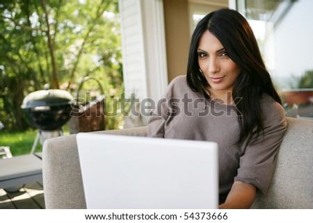 Portrait of a young woman on a sofa with a laptop computer - stock photo