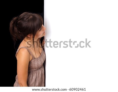 Portrait of a young woman peeking behind empty white wall - stock photo