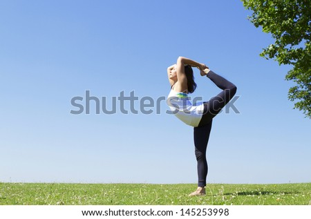 Portrait of a Young Woman performing Yoga outside on grass - stock photo