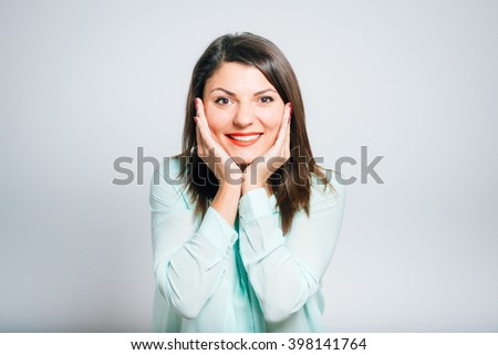 Portrait of a young woman pleasantly surprised, happy emotion - stock photo