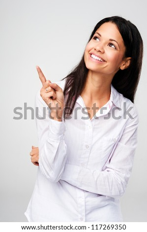 Portrait of a young woman pointing and selecting while happy and smiling isolated on grey background - stock photo