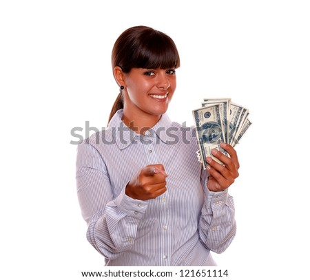 Portrait of a young woman pointing at you and holding dollars on isolated background - stock photo