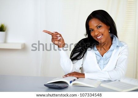 Portrait of a young woman pointing to his right at home - stock photo