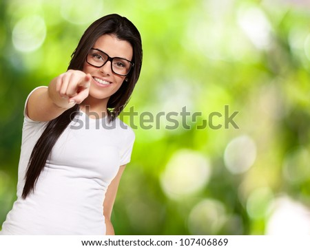 portrait of a young woman pointing with finger against a nature background