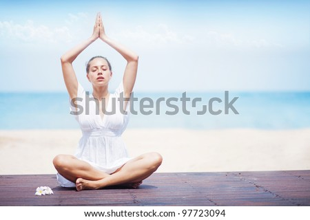 Portrait of a  young woman practicing yoga at the beach - stock photo