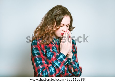 Portrait of a young woman praying, the topic of religion isolated on a gray background - stock photo