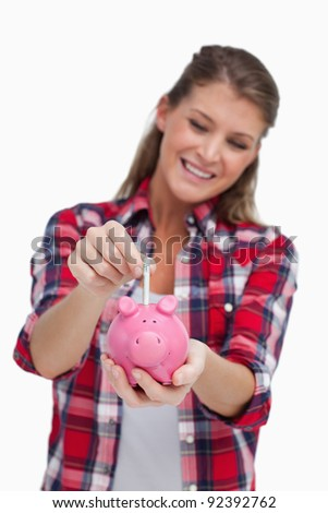Portrait of a young woman putting a note a piggy bank against a white background