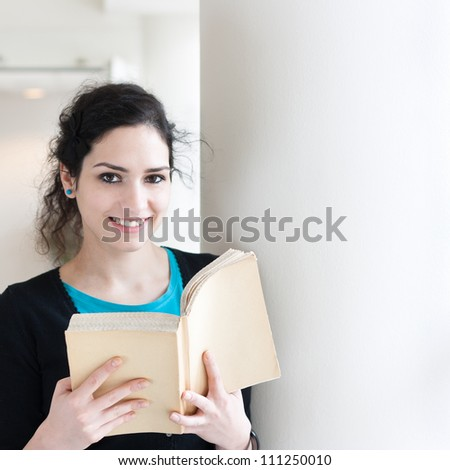 Portrait of a young woman reading a book with copy space - stock photo