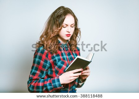 Portrait of a young woman reading a notepad, isolated on a gray background - stock photo