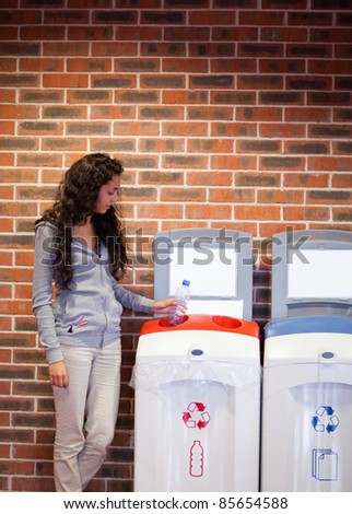 Portrait of a young woman recycling a plastic bottle - stock photo