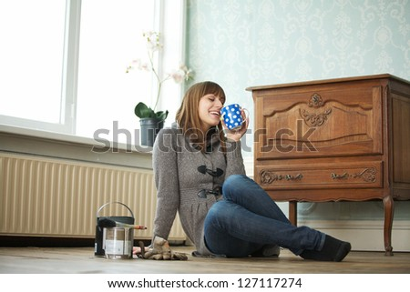 Portrait of a young woman relaxing and drinking a cup of coffee - stock photo