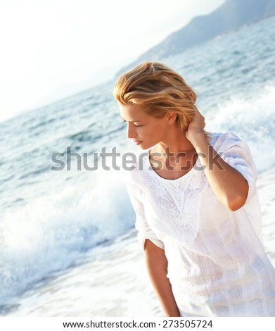 Portrait of a young woman relaxing on the beach - stock photo