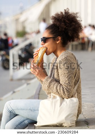 Portrait of a young woman relaxing outdoors and eating food - stock photo